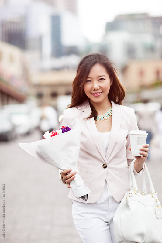 Beautiful happy Asian woman holding a bouquet of flowers and a c by Suprijono Suharjoto for Stocksy United