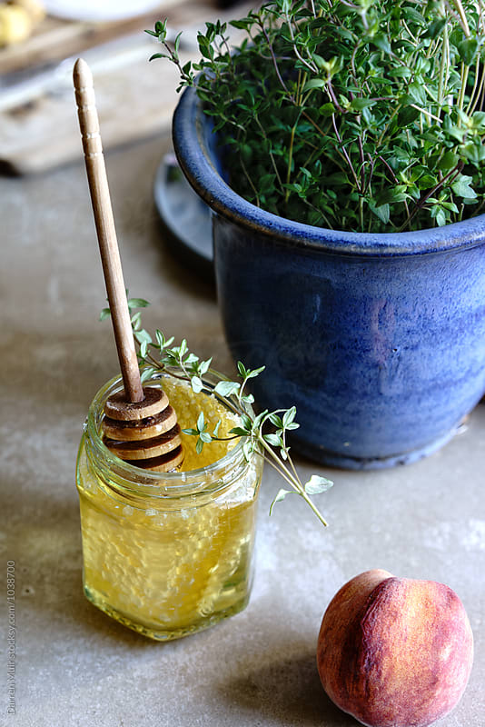 Thyme honey with honeycomb and honey dipper in a glass jar. by Darren Muir for Stocksy United