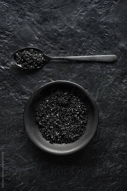 Black charcoal salt on slate  by Jill Chen for Stocksy United