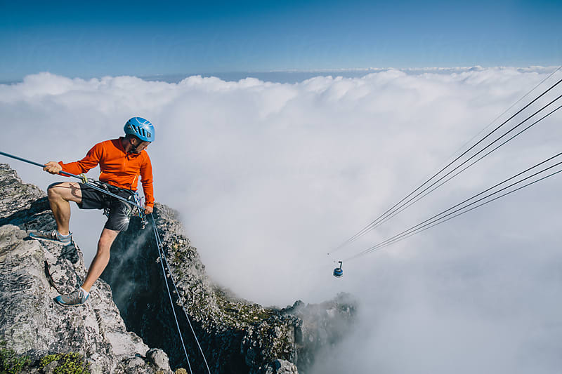 Mountaineer abseiling off the edge of Table Mountain, cable car in the distance by Micky Wiswedel for Stocksy United
