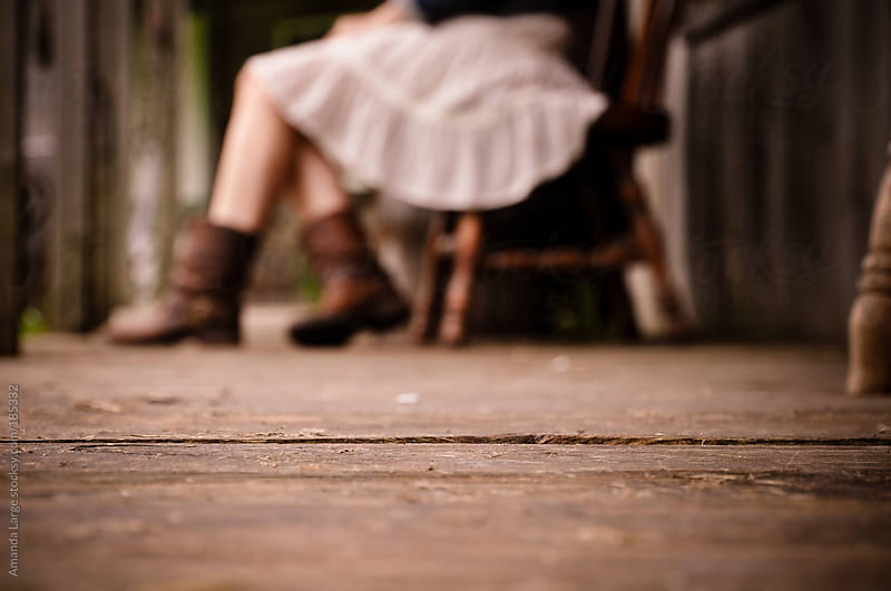 girl wearing skirt and boots sitting on a wooden porch by Amanda Large for Stocksy United