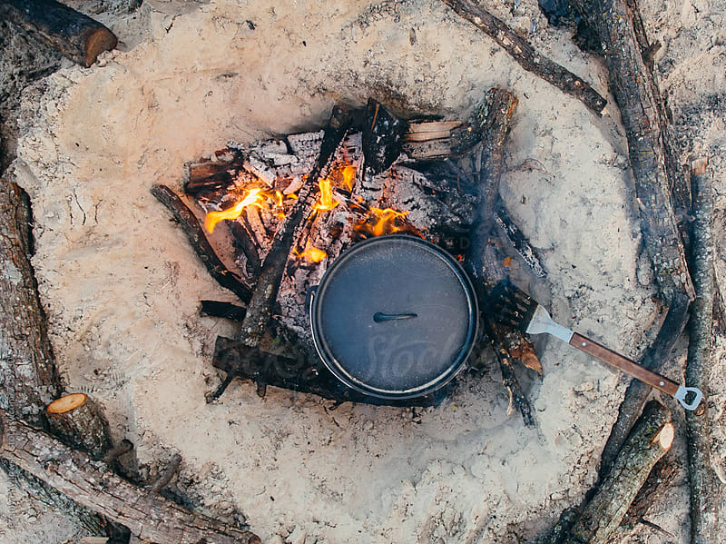 Camp cooking, cast iron with fire on the beach. by Jeremy Pawlowski for Stocksy United