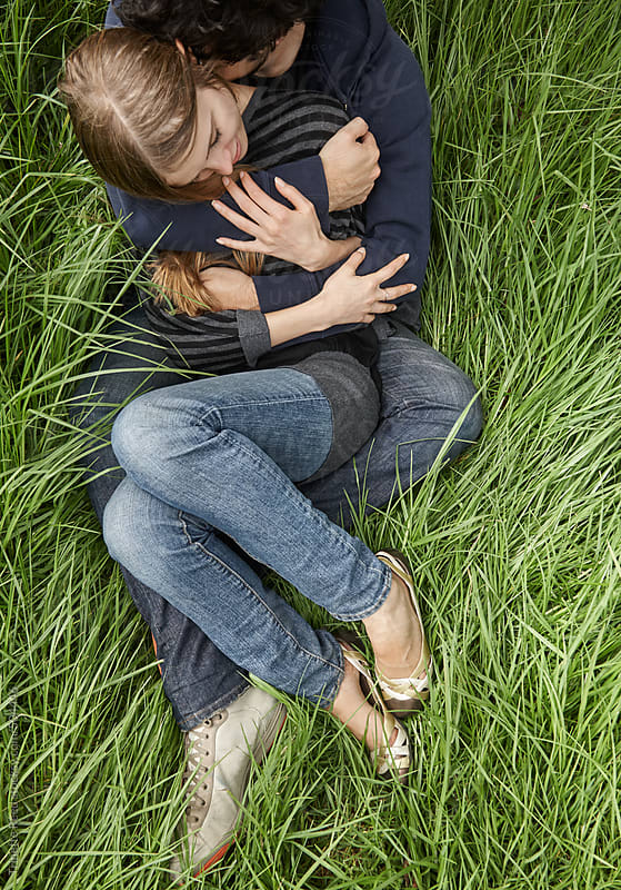 Couple embracing in the grass in nature in California  by Trinette Reed for Stocksy United