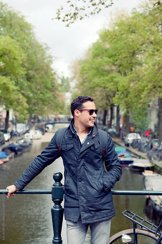 Young man in Amsterdam standing on a bridge with a canal, boats and trees in the background by Ivo de Bruijn for Stocksy United