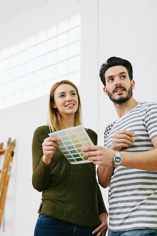 Young couple holding swatch colours for the new home. by BONNINSTUDIO for Stocksy United