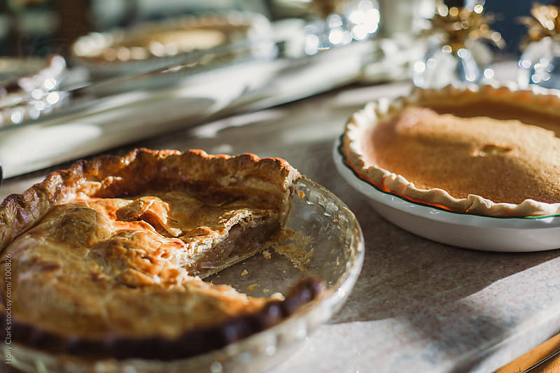 Homemade apple and pumpkin pies on a marble-topped table. by Holly Clark for Stocksy United