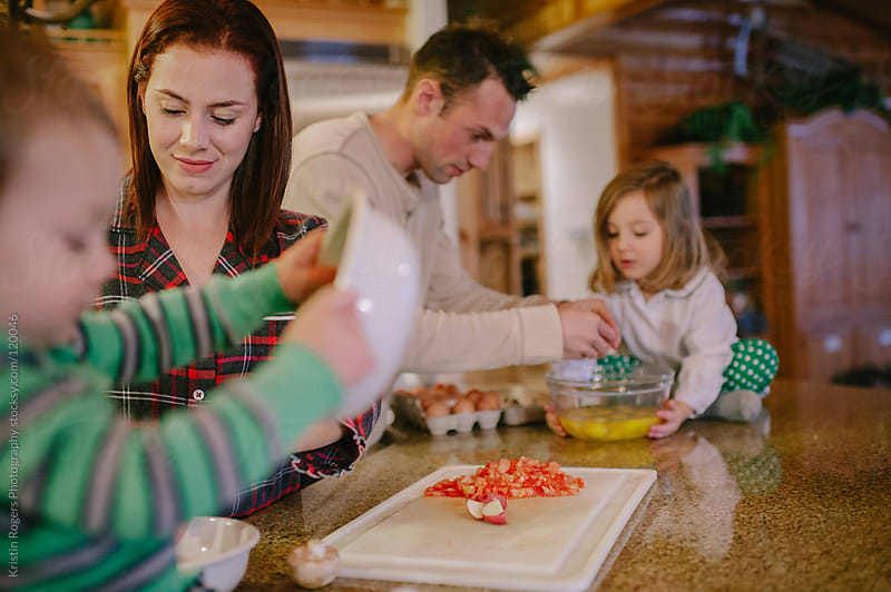 Family making meal in cabin by Kristin Rogers Photography for Stocksy United