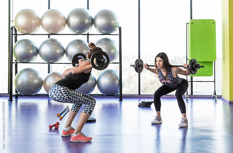 Two female athletes doing squats with barbells in a studio by Lior + Lone for Stocksy United