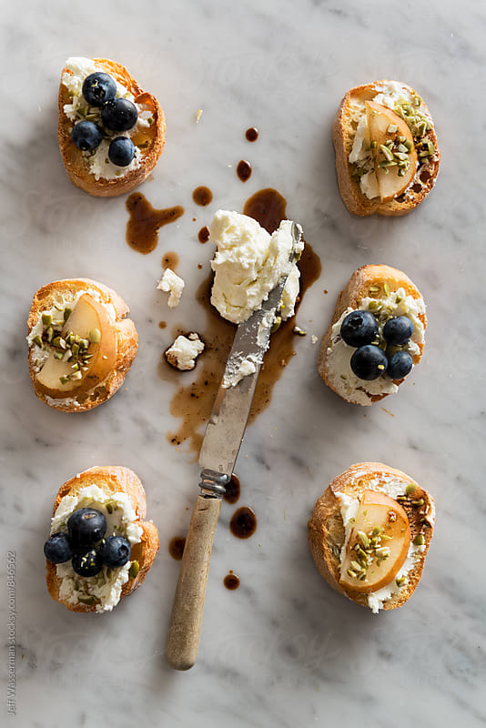 Crostini with Goats Cheese, Pear and Blueberry From Overhead by Jeff Wasserman for Stocksy United