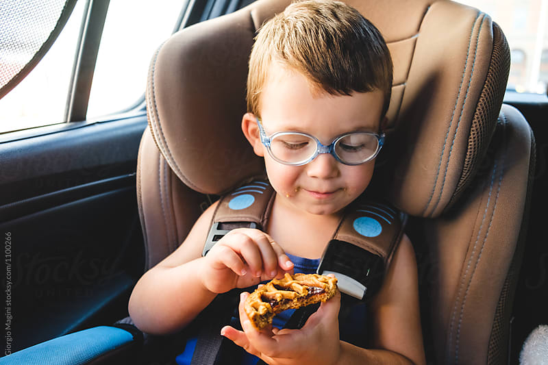 Toddler Boy Eating a Small Tart in a Baby Car Seat by Giorgio Magini for Stocksy United