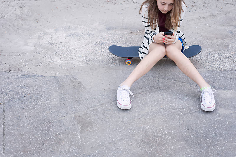 Teen girl sitting on her skateboard and playing with her cell phone by Carolyn Lagattuta for Stocksy United