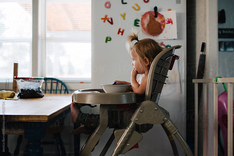 Toddler sitting in high chair in kitchen by Jessica Byrum for Stocksy United