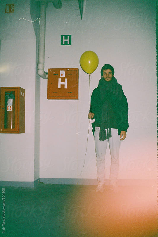 Image from analog camera of a young man holding yellow balloon in the parking lot by Nabi Tang for Stocksy United