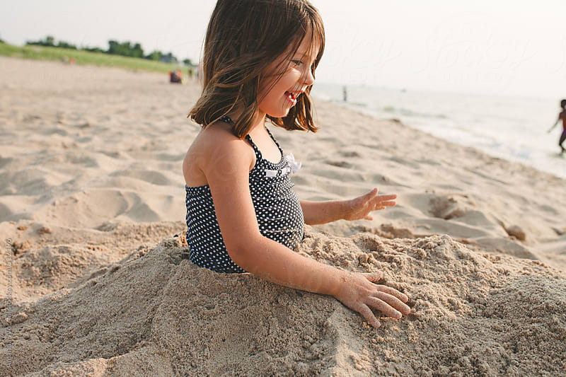 Smiling young girl buried in sand at the beach by Amanda Worrall for Stocksy United