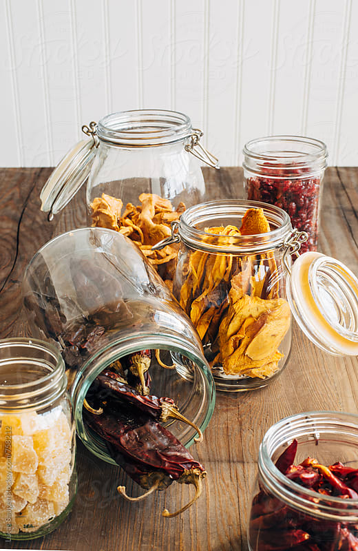 Open jars with dried fruits and peppers spilling out. by Lucas Saugen for Stocksy United