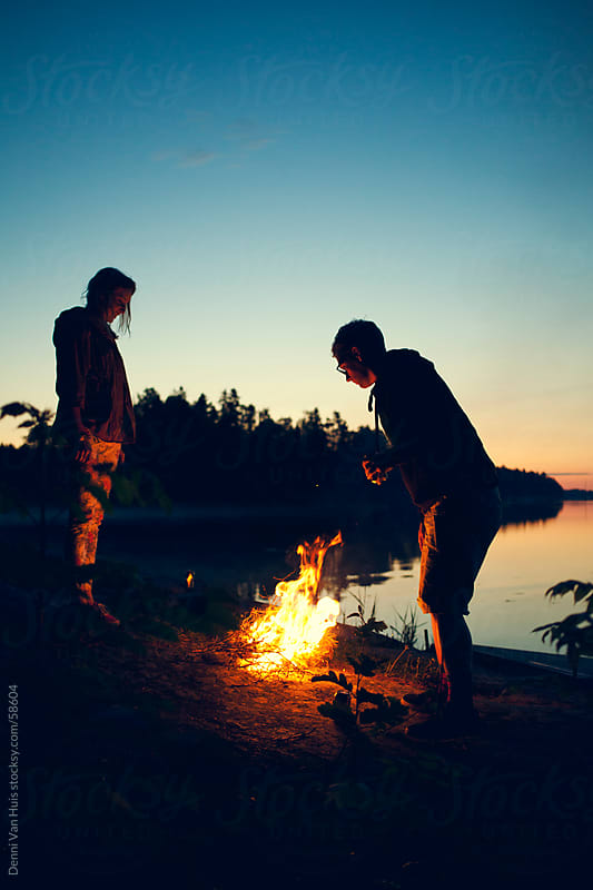 Two people enjoying a campfire right next to a lake on a summer night by Denni Van Huis for Stocksy United