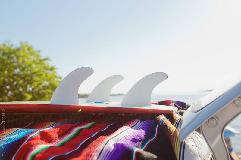 surfboard sits on top of vehicle by Tana Teel for Stocksy United