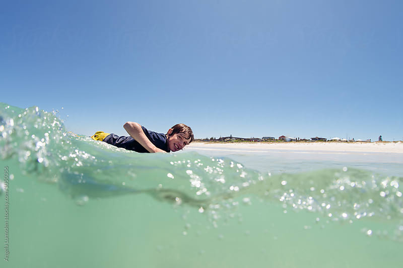Over under image of a boy riding a low wave on a boogie board at the beach in summer by Angela Lumsden for Stocksy United