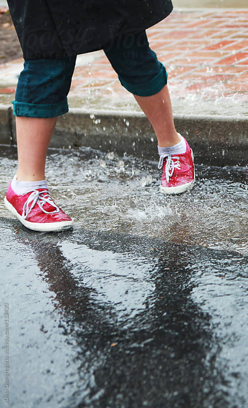 Child playing in the rain showing legs and wet shoes only by Dina Giangregorio for Stocksy United