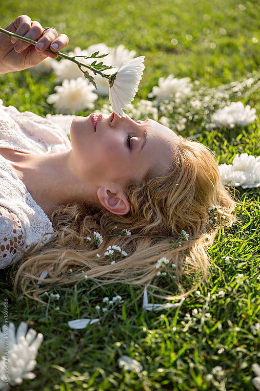 Beautiful blonde woman lying on green grass and smelling white flowers  by Jovo Jovanovic for Stocksy United