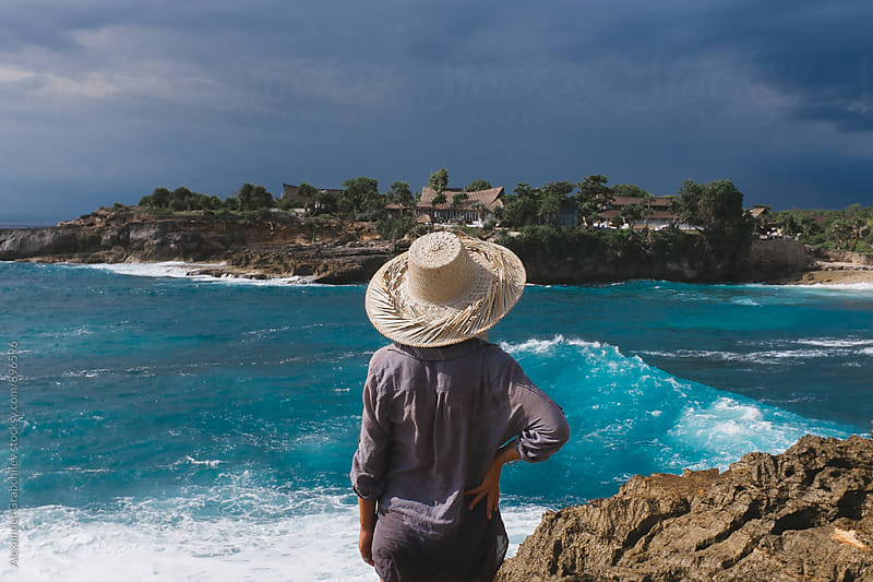Woman In Straw Hat Standing On Rocky Beach, Back View. by Alexander Grabchilev for Stocksy United