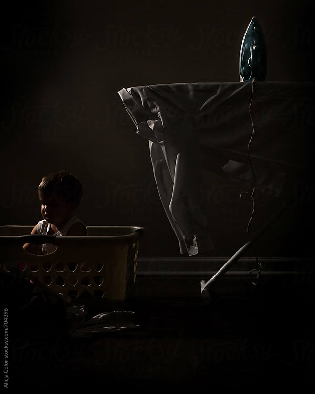 Moody child in laundry basket by Alicja Colon for Stocksy United