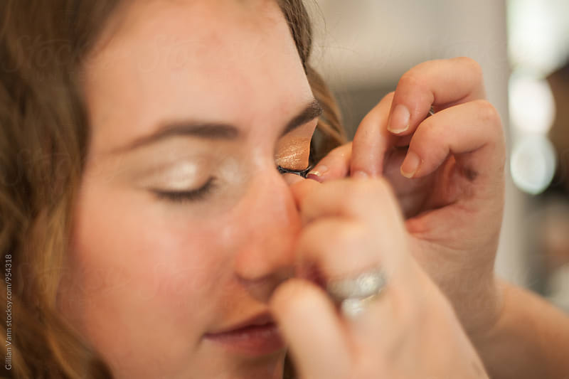 applying false eyelashes to a woman's face, the before shot by Gillian Vann for Stocksy United