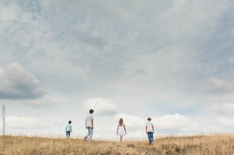 Backside of four kids walking in a field on a cloudy summer day by Cindy Prins for Stocksy United