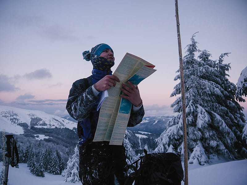 Hiker checking his map in snowy forest by Martin Matej for Stocksy United
