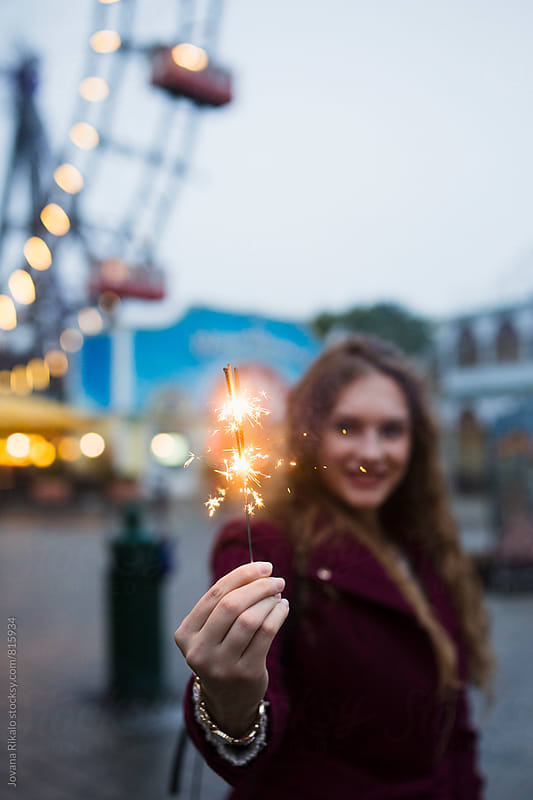 Young woman holding sparkler and smiling by Jovana Rikalo for Stocksy United
