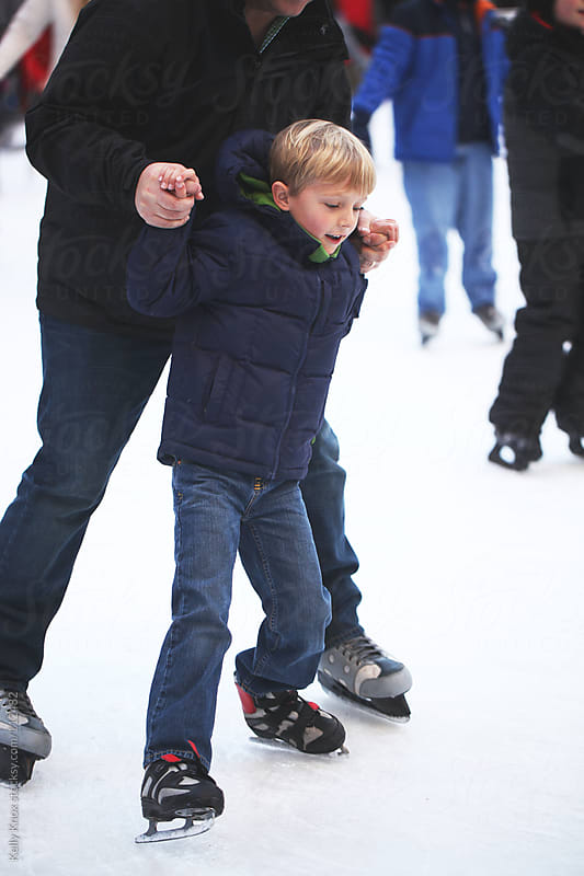 father and son ice skating by Kelly Knox for Stocksy United