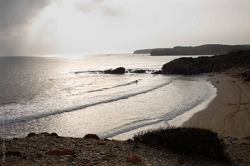 Lonely fisherman in a beach of the mediterranean island of Menorca by Miquel Llonch for Stocksy United