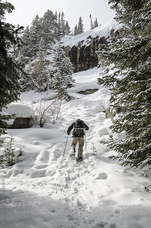 Man snowshoeing in the Colorado Rockies by Julie Rideout for Stocksy United