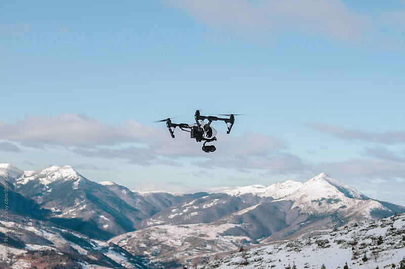 drone flying above snowcovered mountain landscape by Leander Nardin for Stocksy United