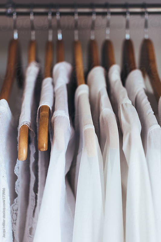 White shirts hanging in a wardrobe by Jacqui Miller for Stocksy United