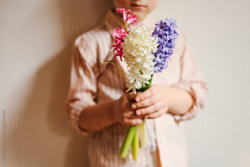 Kid holding a bouquet, just body by Marija Kovac for Stocksy United