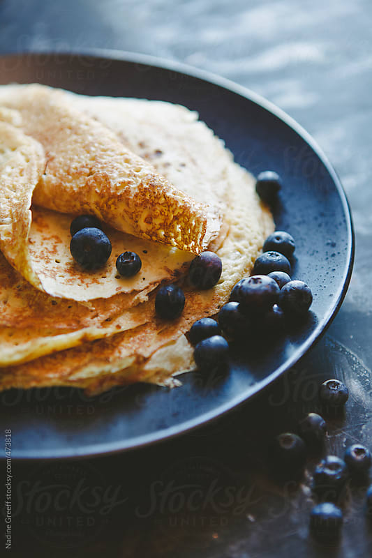 Crepes or Thin Pancakes with fresh blueberries by Nadine Greeff for Stocksy United