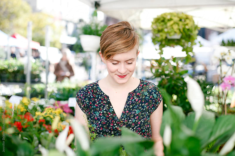 A young woman shops for plants by Jennifer Brister for Stocksy United