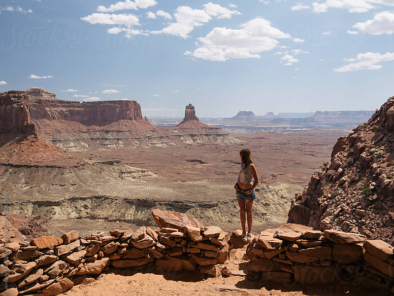 Young woman in crop top looking out over vast canyon after hiking by Jeremy Pawlowski for Stocksy United