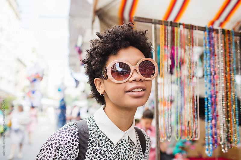 Beautiful afro woman wearing a pair of sunglasses by michela ravasio for Stocksy United