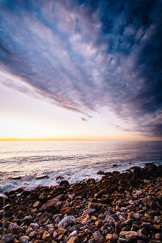 Sunset over a rocky shore by Micky Wiswedel for Stocksy United