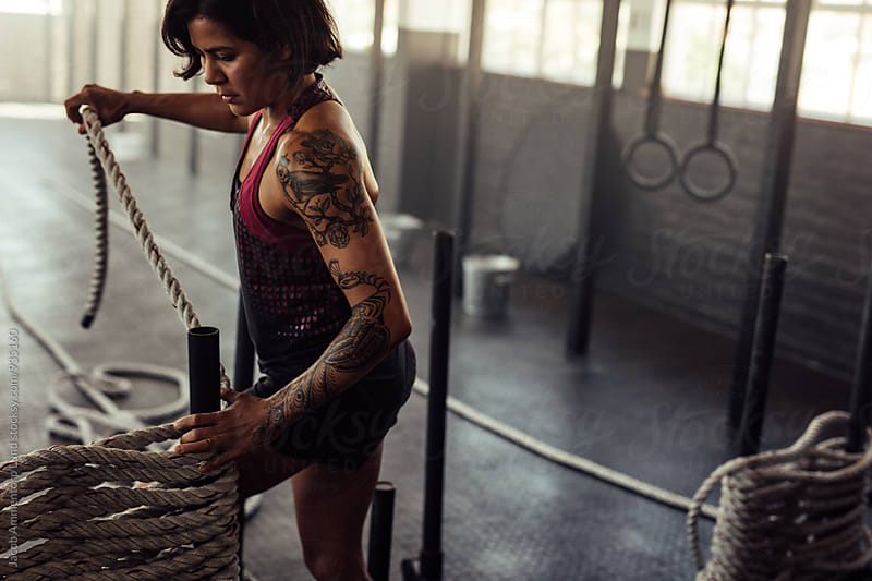 Tattooed woman with battling ropes at gym by Jacob Lund for Stocksy United