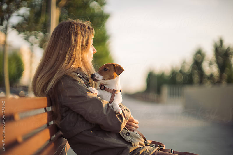 Woman sitting on a bench with dog by Javier Pardina for Stocksy United