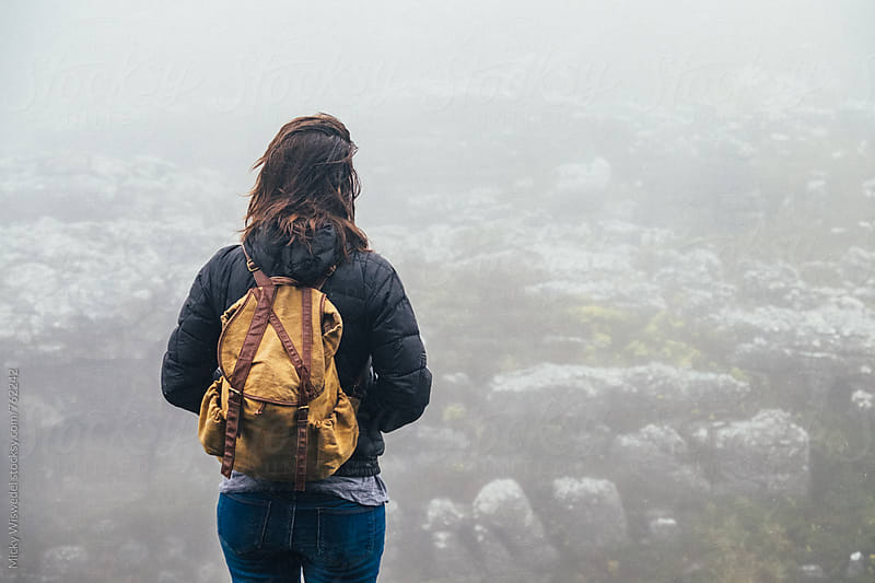 Woman with a backpack in a misty mountain environment by Micky Wiswedel for Stocksy United