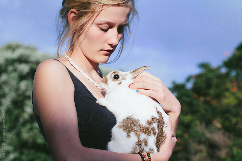 Girl holding a white pet rabbit by Jacqui Miller for Stocksy United