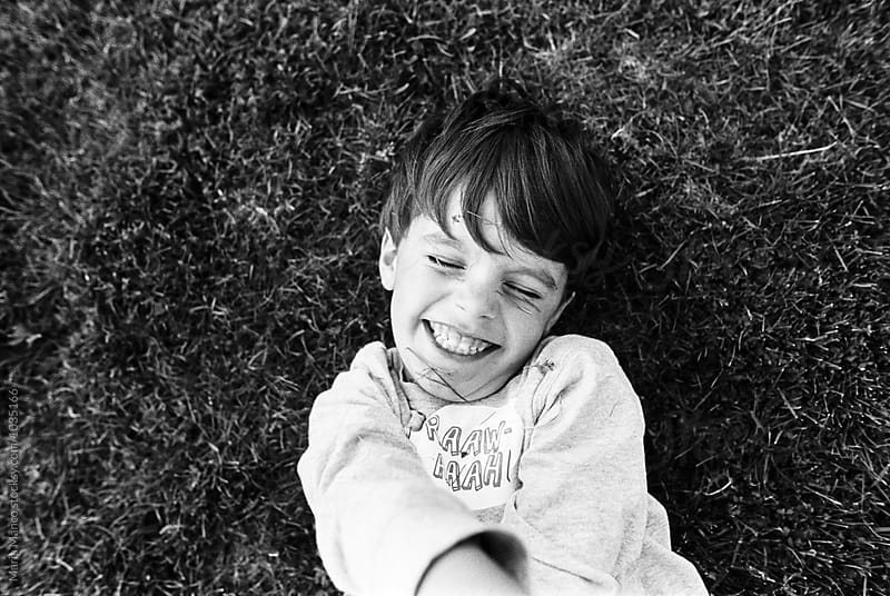 boy laughs in grass by Maria Manco for Stocksy United