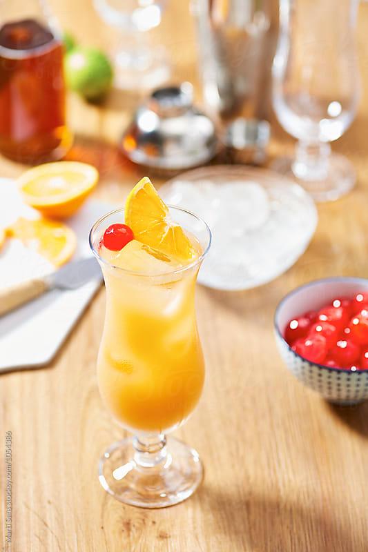 Tasty hurricane cocktail served with dessert cherry and orange segment by Martí Sans for Stocksy United