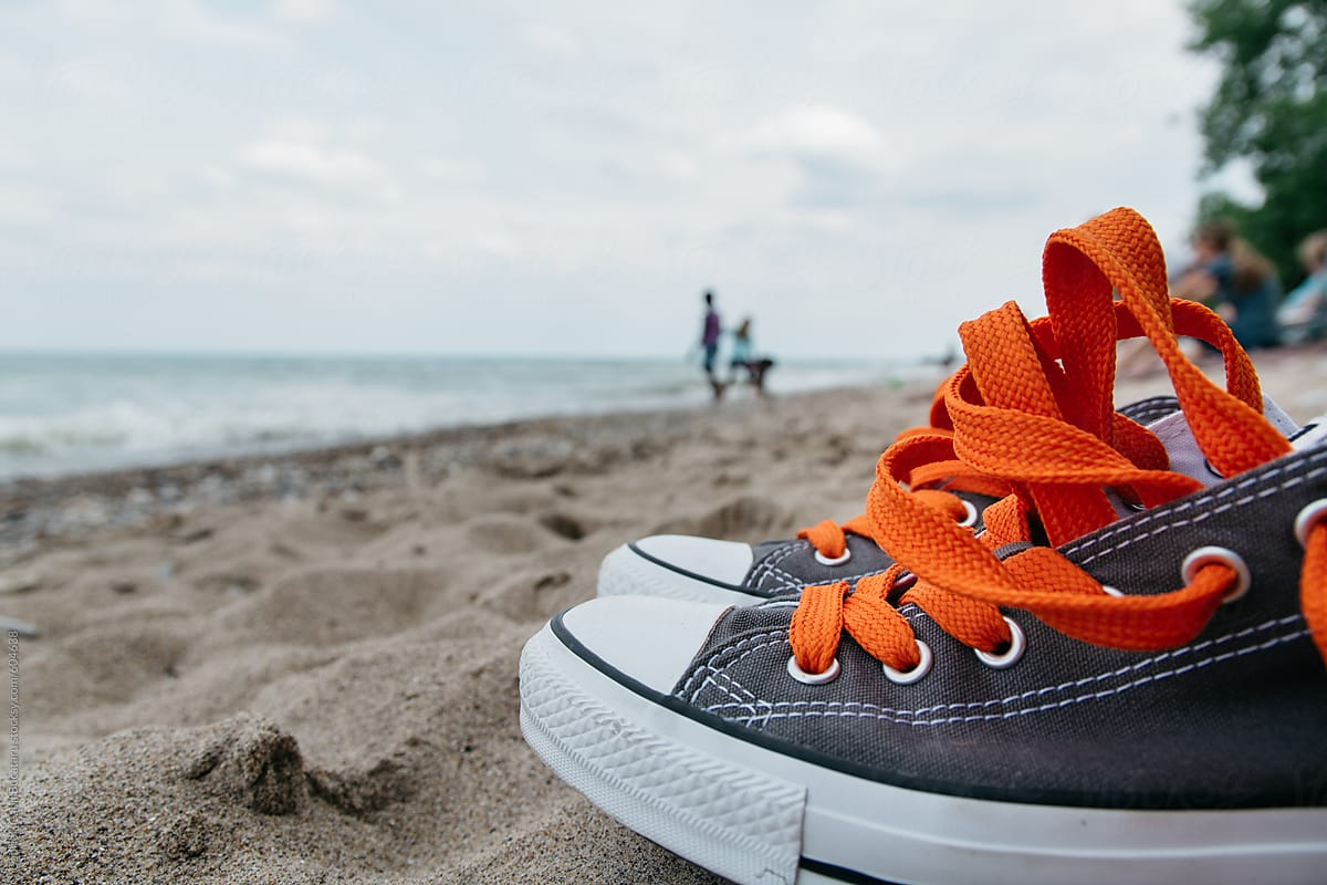 Tennis shoes with orange laces on a