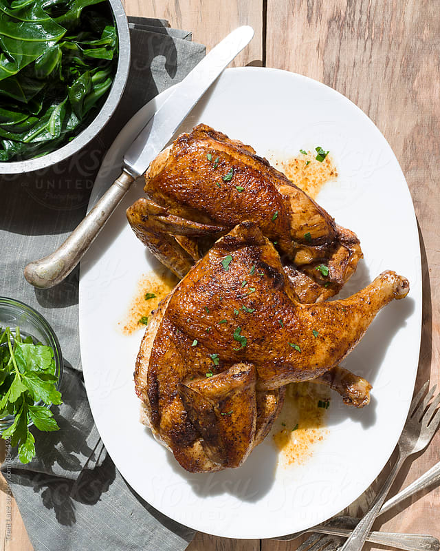 Roasted organic chicken with seasoning and collard greens by Trent Lanz for Stocksy United