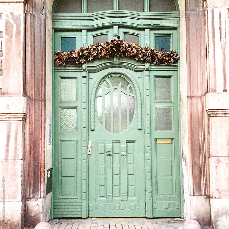 Green decorated door by Jovana Rikalo for Stocksy United